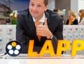 Herr Matthias Lapp vor dem neuen Logo
